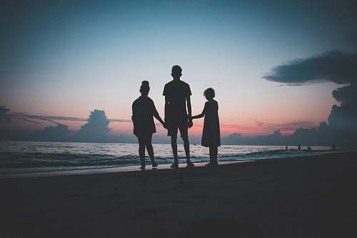human silhouette of three people walking beside body of water people