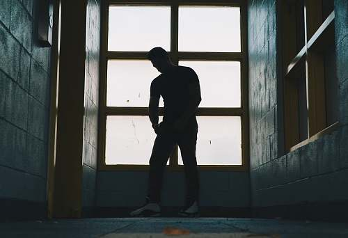 people silhouette photo of a man standing near glass window human