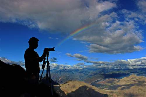nature silhouette photo of holding camera with stand during daytime with rainbow sky