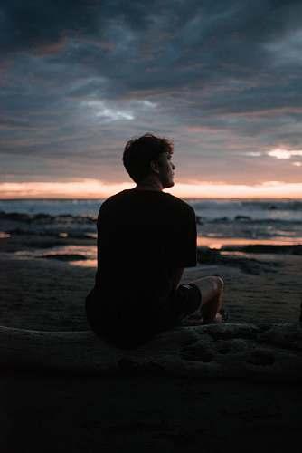 human silhouette photo of man sitting on beach silhouette