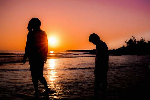 human silhouette photography of boy and girl standing at beach nature