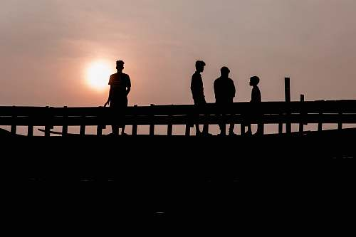 water silhouette photography of four people waterfront