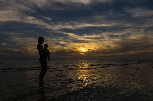 nature woman carrying baby on seashore during sunset human