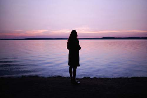 people woman standing near body of water during golden hour human