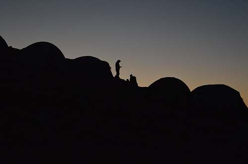 dusk A silhouette of a person in a camping site on a slope at night sunrise