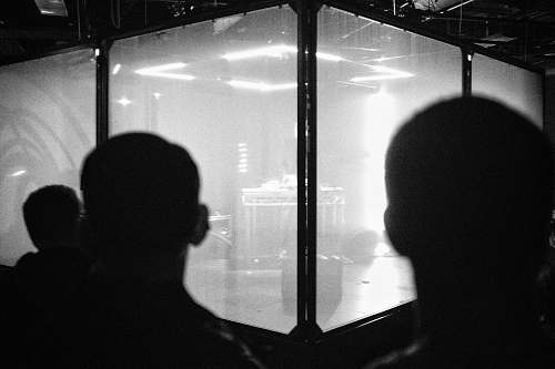 black-and-white backview of people looking to glass room grey