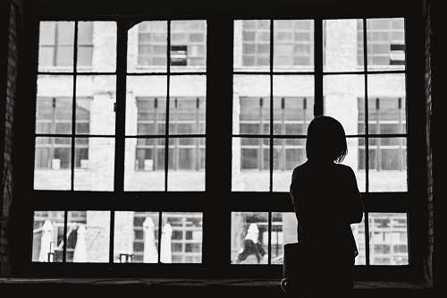 black-and-white grayscale photography of woman facing window window