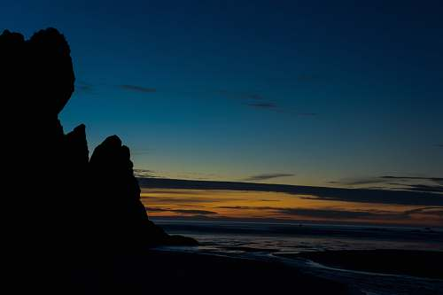 nature landscape photography of rock formation near body of water during nightime ruby beach
