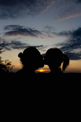 nature man and woman kissing during golden hour human