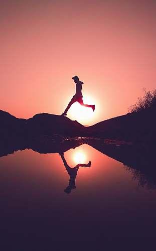 nature man jumping on rock beside lake outdoors