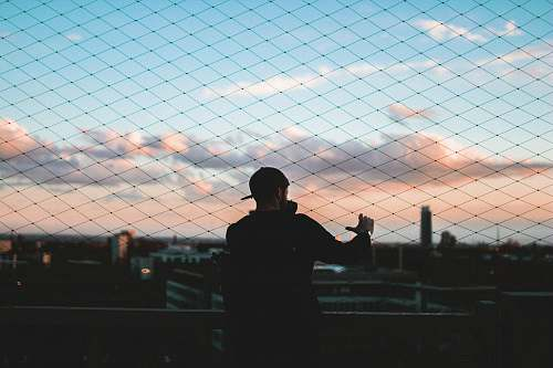 person man standing behind chain link fence holding to fence during golden hour skyline