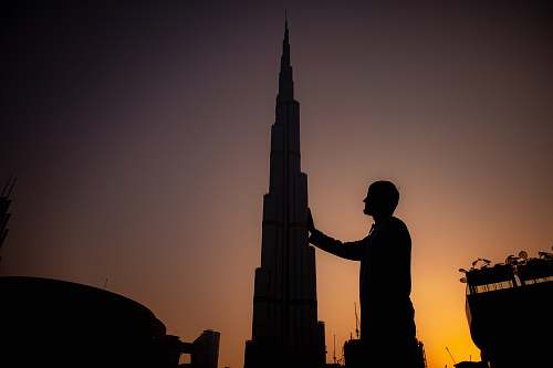 architecture man standing near Burj Khalifa during sunset building