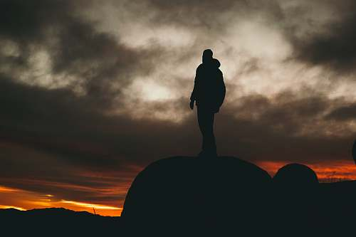 standing man standing on rock during golden hour nature