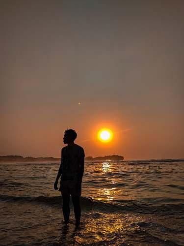 sunset man standing on seashore during sunset nature