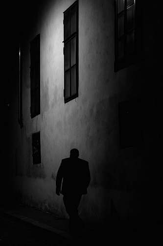 photo person man walking beside gray concrete wall during night time black-and-white free for commercial use images