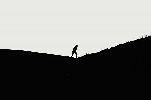 black-and-white man walking on hill standing