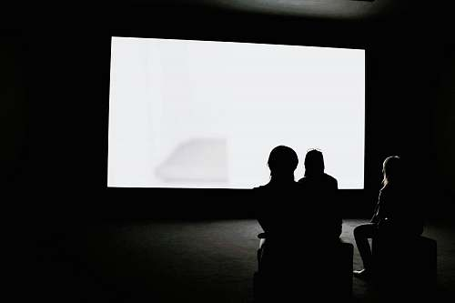 black-and-white people looking on projection screen white