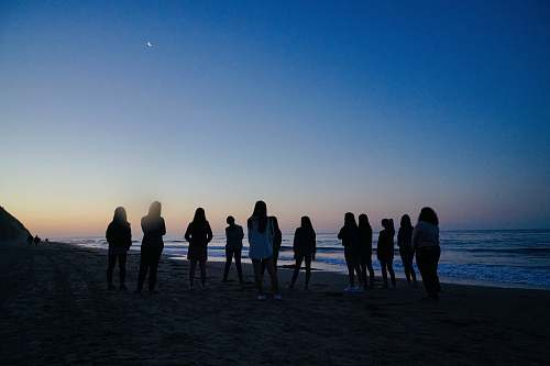 human people standing beside sea during nighttime person