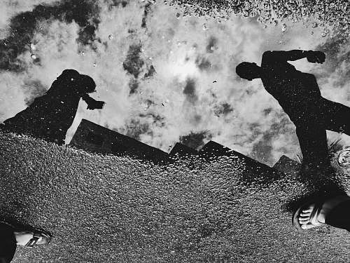 black-and-white reflection of two people on water puddle grey