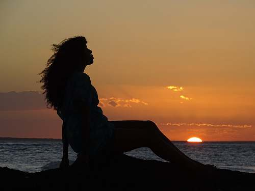 nature silhouette of a woman sitting on the ground during golden hour outdoors
