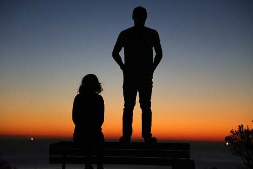 human silhouette of an standing man and sitting woman on bench people