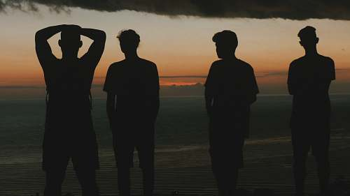 human silhouette of four men at the beach person