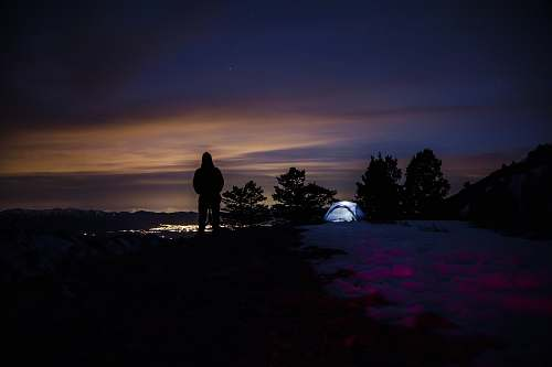 person silhouette of hooded person with tent in background camping