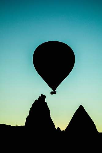 photo hot air balloon silhouette of hot air balloon flying above rock formation cappadocia free for commercial use images