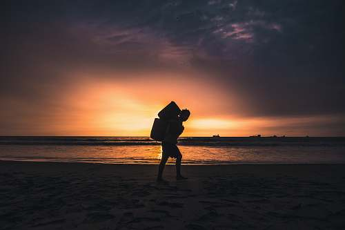 nature silhouette of man carrying container standing on shoreline outdoors