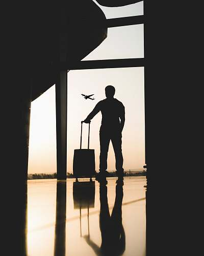 person silhouette of man holding luggage inside airport people