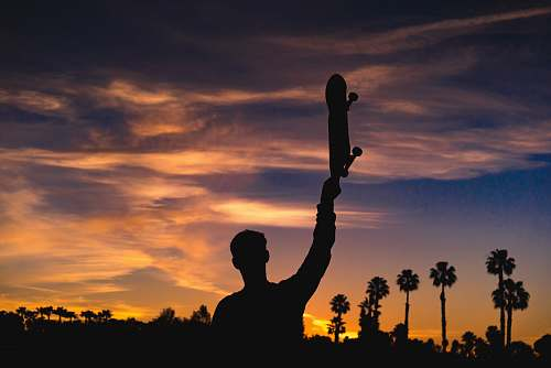 person silhouette of man holding skateboard human
