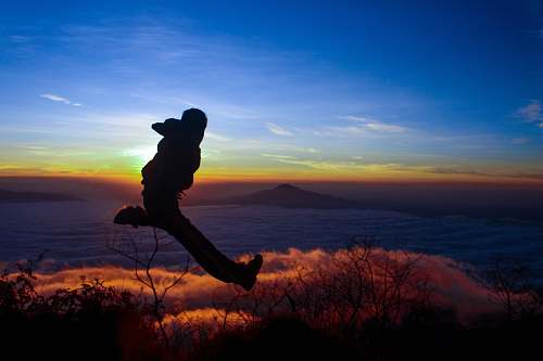 nature silhouette of man jumping on mid air outdoors