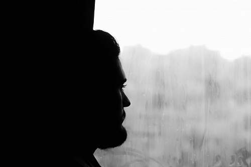 black-and-white silhouette of man near window grey