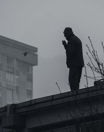 human silhouette of man on roof person