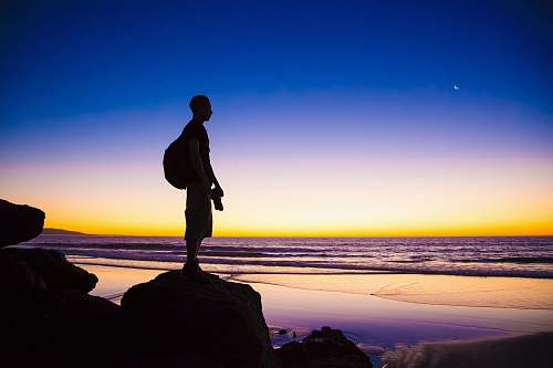 person silhouette of man standing on cliff shore