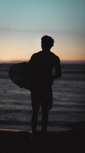 nature silhouette of man standing on shore holding bodyboard ocean