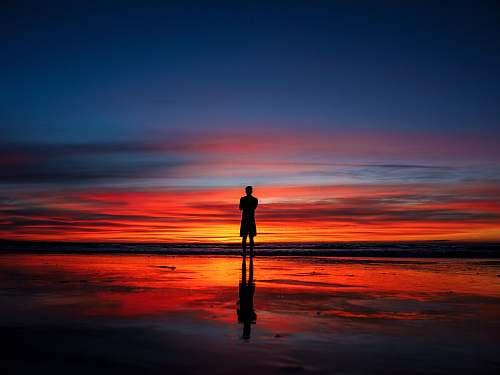nature silhouette of man standing on shoreline at night time sunset
