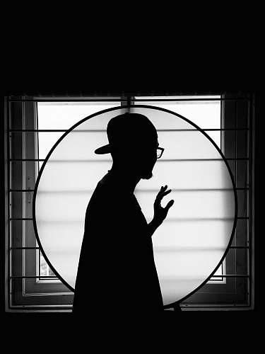 black-and-white silhouette of man standing on window person