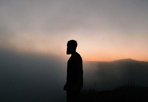 human silhouette of man surrounded with fog during golden hour person