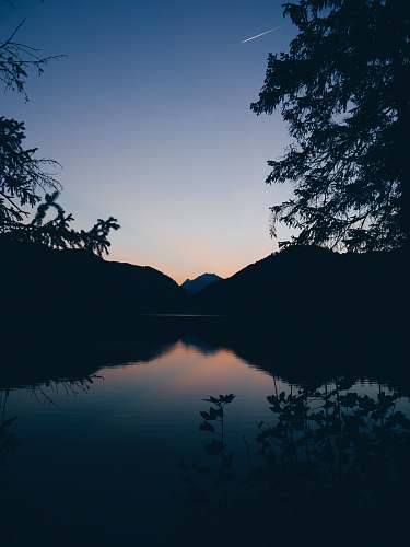 nature silhouette of mountain, lake and trees in nature photography outdoors