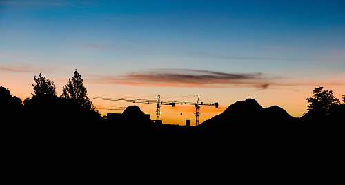 nature silhouette of mountain construction crane
