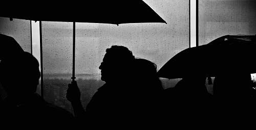 human silhouette of people holding umbrella black-and-white