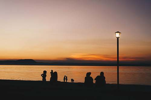 human silhouette of people near seashore viewing lighted lamp post person