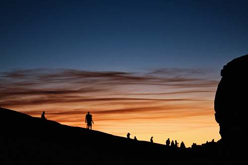 sky silhouette of people on mountain under blue sky during sunset sunrise