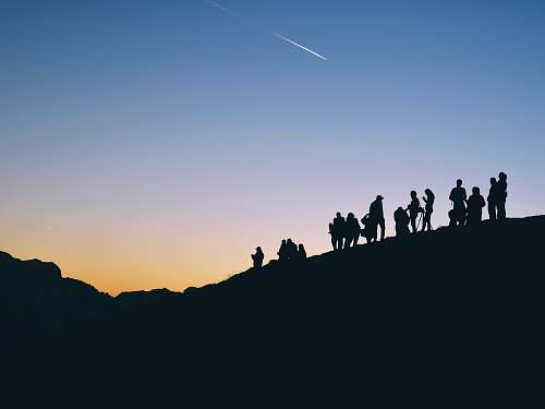 sunset silhouette of people on mountain under falling satr sky