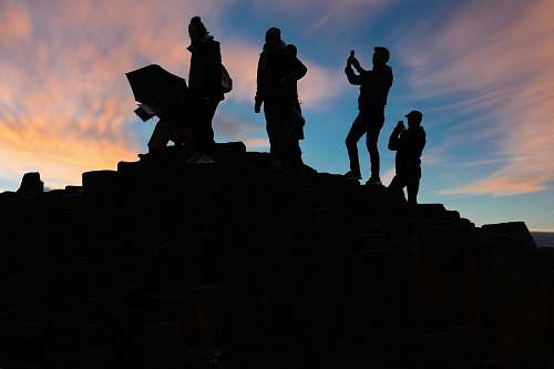 person silhouette of people standing on top of mountain during sunset human
