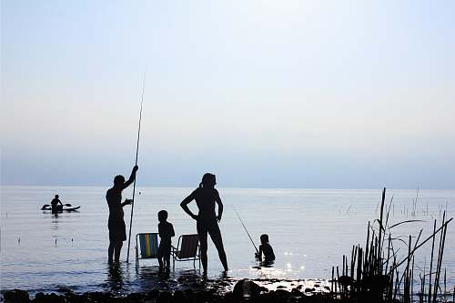 fishing silhouette of people standing on water during daytime family