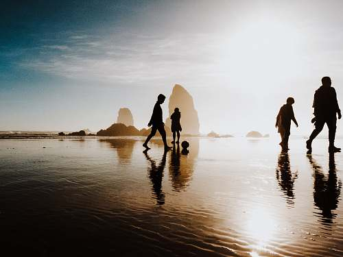 haystack rock silhouette of people walking body of water united states