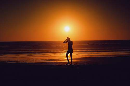 beach silhouette of person beside seashore during sunset ocean