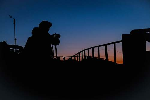 human silhouette of person holding DSRL camera railing
